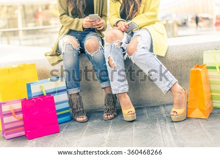 Two girls sitting in a shopping center and looking at smart phones - Girlfriends with shopping bags, close-up on low section body - stock photo