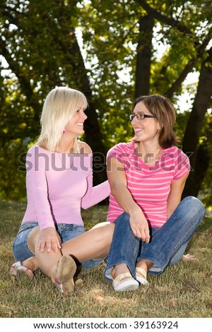 two girls sitting in the grass and talking - stock photo