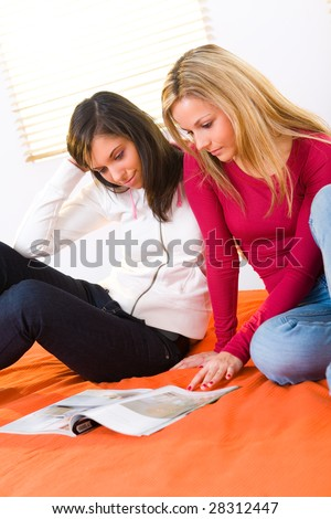 Two girls sitting on bed and browsing magazine. - stock photo