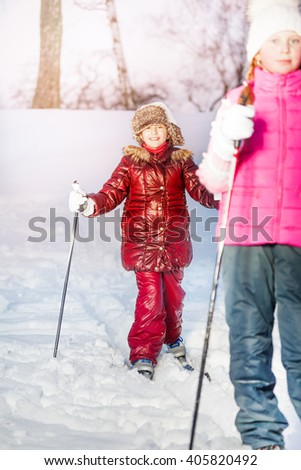 Two girls skiing in the white winter forest - stock photo