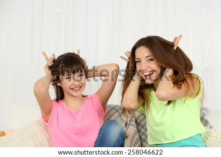 Two girls smiling on home interior background - stock photo