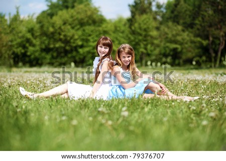 two girls spending time together in the summer park