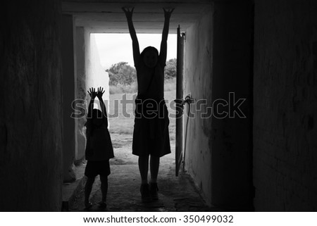 Two girls standing and playing in an old war tunnel. With the day light behind them, it makes a wonderful silhouette that could be used for a variety of ideas and concepts. Black and white, horizontal - stock photo