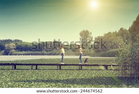 Two girls standing on wooden dock on lake and holding dog on leash - stock photo