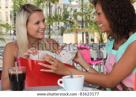 Two girls stopping for coffee on a shopping trip - stock photo