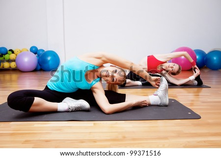 Two girls stretching in fitness club
