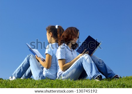 Two girls students sitting on grass studying in the nature reading books - stock photo