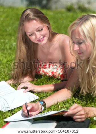 two girls study outside in the park - stock photo