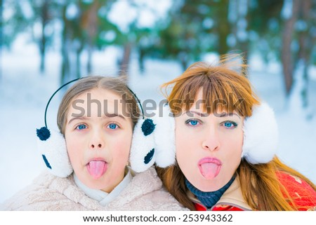 two girls surprised faces on snow background. surprise winter discounts. Mom and daughter in the park in winter, cheerful two girls in the winter forest, two funny portrait in winter - stock photo