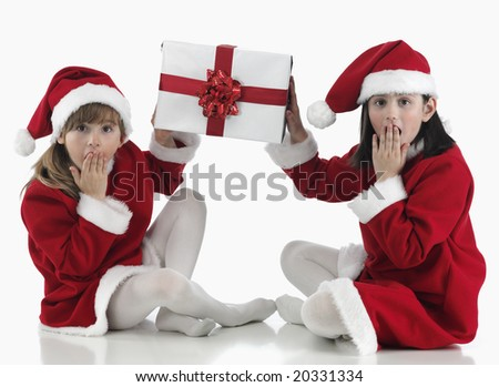 two girls surprised with Christmas hat and presents - stock photo