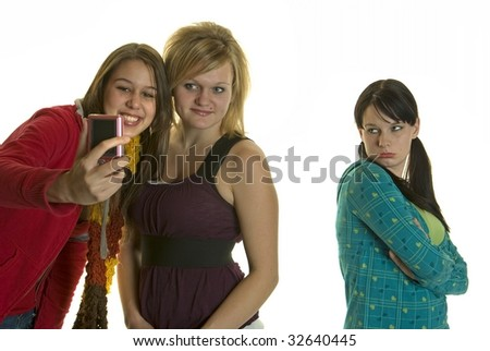 Two girls take photo or video of themselves and leave out third girl - stock photo