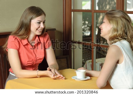 Two girls talking at a cafe table. Girls drink cherry juice sitting by the window