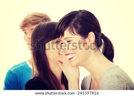 Two girls talking gossip about boy - stock photo
