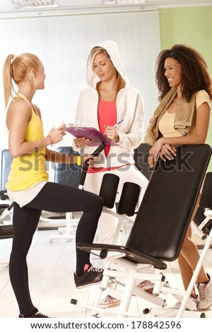 Two girls talking to personal trainer at the gym. - stock photo