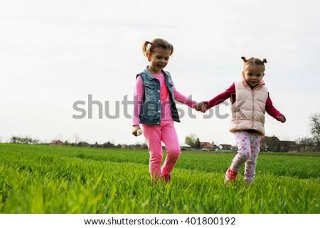 Two girls walking and having fun on meadow. - stock photo