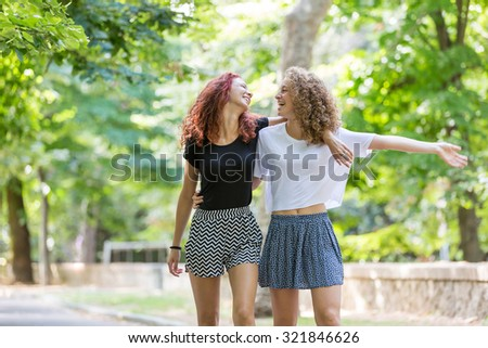 Two girls walking embraced at park. . They are two young girls walking embraced and  smiling to each other. They are having fun together on a summer day. - stock photo