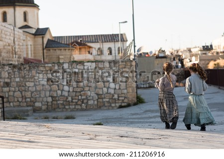 Two girls walking in the Old City in Jerusalem in Israel at the foot of the western side of the Temple Mount. - stock photo