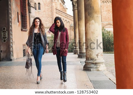 Two girls walking outdoors in Saint Stephen square, Bologna, Italy. Full body. - stock photo
