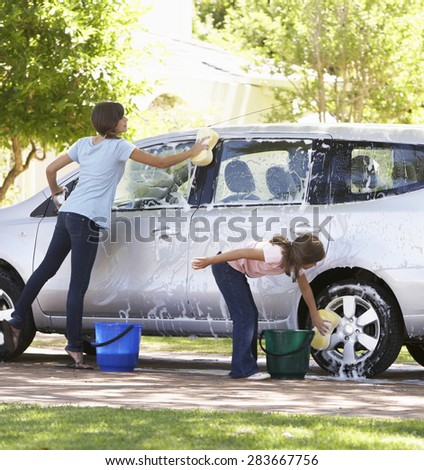 Two Girls Washing Car Together - stock photo