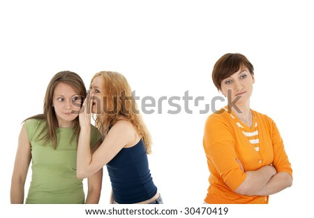 Two girls whispering secrets to each other, and their friend, upset and rejected - stock photo