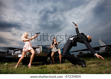 Two girls with arms shooting at guy - stock photo
