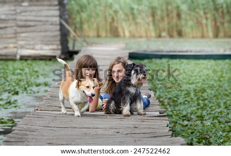 Two girls with dogs lying on wooden dock on the lake - stock photo