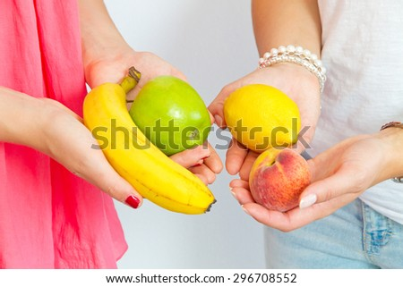 Two girls with fruits in the hands