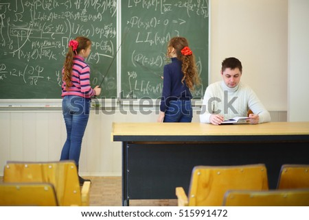 Two girls with pointers stand near blackboard with formulas and teacher looks into book in classroom, focus on man