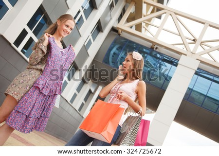 Two girls with shopping bags standing on the street,one of the girls envies of new dress another girl - stock photo