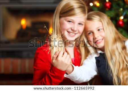 two girls with sparklers smiling focus on sparklers - stock photo