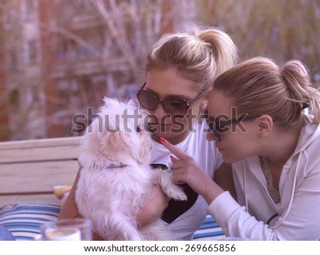 Two girls with their dog in coffee house enjoying on the sun - stock photo