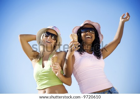 two girlseating ice-cream and laughing - stock photo