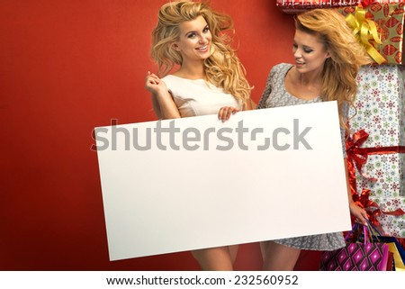 Two glamorous women holding sale board - stock photo