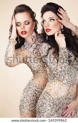 Two Glamorous Women in Evening Dresses and Jewelry Dancing - stock photo