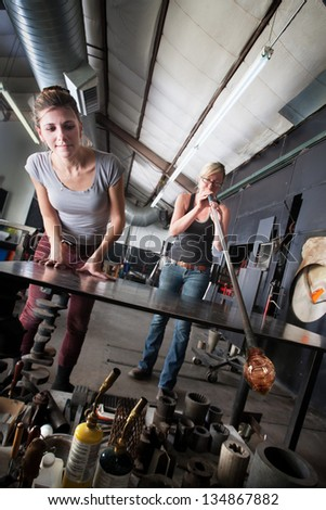 Two glass artists working together on clear vase - stock photo