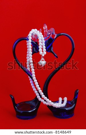 Two glass blue swans with a pearl on red - stock photo