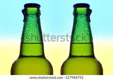 Two glass bottles of beer with dewdrops