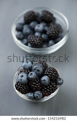 Two glass bowls full of ripe blackberries and blueberries