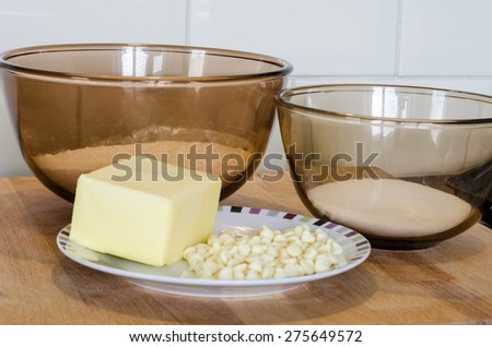 Two Glass Bowls of Baking Ingredients - Flour Sugar and Butter - on a Plate with White Chocolate Chips on Wooden Board. All baking ingredients on top of a wood surface. Horizontal. Landscape. - stock photo