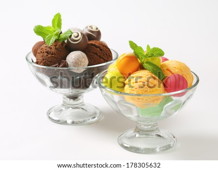 Two glass cups with fruit pralines and chocolate truffles assorted with ice cream - stock photo