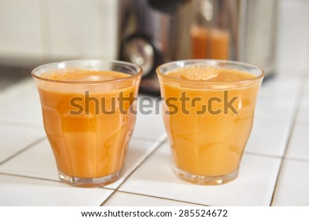 Two glass of carrot juice on the table - stock photo