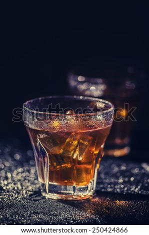 Two glass of iced cocktail on wet background. Vintage filter. - stock photo