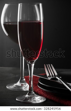 Two glass of red wine, plates and silverware on dark wooden table. Shallow DOF. - stock photo