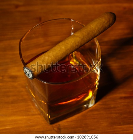 two glass of whiskey and cigar on wooden table