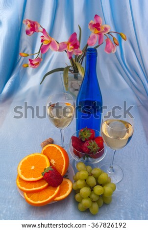 Two glass of white wine and blue bottle with oranges, red strawberry, green grapes and orchid - stock photo