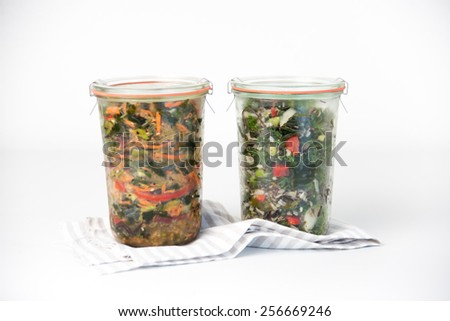 Two Glass Weck Jars with Green Salads in Them  - stock photo