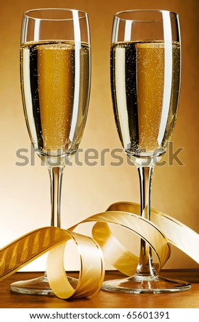 Two glass with champagne and celebratory ribbon - stock photo