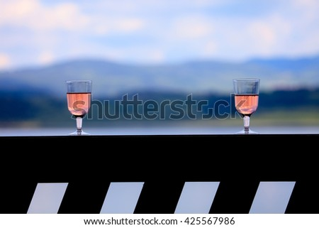 two glass with rose wine over the sunset near mountain lake, romance for two conceptual landscape