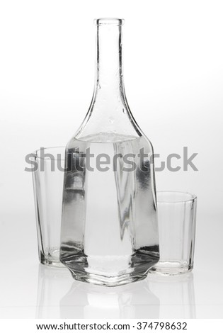 Two glasses and a decanter on grey white background - stock photo