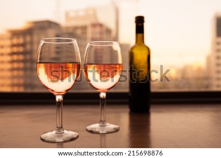 Two glasses and bottle of white wine with the city background - stock photo